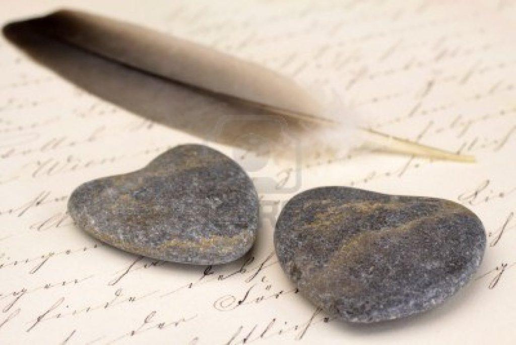 13779814-twee-stenen-harten-met-veren-en-oude-brief